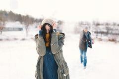 Жизнерадостные пары играя снежные комья в снежном поле в зиме стоковое фото
