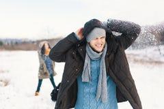 Жизнерадостные пары играя снежные комья в снежном поле в зиме стоковое изображение rf