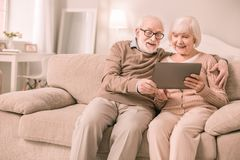 Жизнерадостные пенсионеры имея видеоконференцию с детьми стоковые изображения