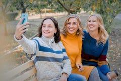 Жизнерадостные привлекательные 3 лучшего друга молодых женщин имея потеху совместно снаружи и делая selfie стоковые изображения rf