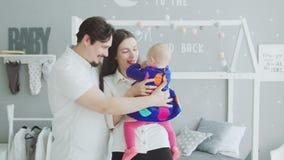 Жизнерадостные родители связывая с младенцем дома акции видеоматериалы