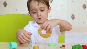 Жизнерадостные, смеясь игры мальчика с моделируя смесью для работы Ребенок ваяет platinina сидя на таблице сток-видео