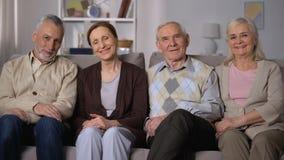 Жизнерадостные старшие друзья сидя на софе и усмехаясь на камере, счастливом выходе на пенсию сток-видео