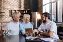 Жизнерадостные старшие пары смотря радостный иметь гостя дома Стоковые Фото