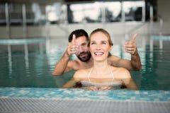 Жизнерадостные счастливые пары ослабляя в бассейне Стоковое фото RF