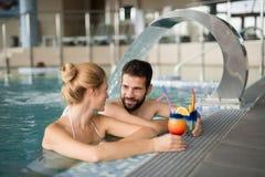 Жизнерадостные счастливые пары ослабляя в бассейне Стоковые Фото