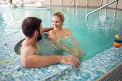 Жизнерадостные счастливые пары ослабляя в бассейне Стоковая Фотография