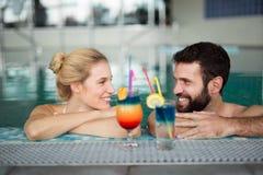 Жизнерадостные счастливые пары ослабляя в бассейне Стоковое Изображение RF