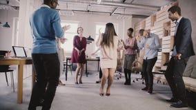 Жизнерадостные танцы коммерсантки на партии вскользь офиса teambuilding Многонациональное команды доли потехи времени замедленное видеоматериал