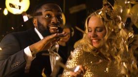 Жизнерадостные танцы пар смешанн-гонки на партии под падая confetti, торжестве акции видеоматериалы