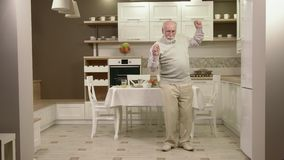 Жизнерадостные танцы старика в кухне сток-видео