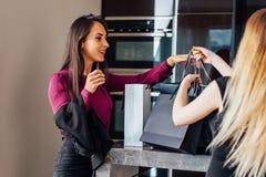 Жизнерадостные элегантные девушки стоя в стильном интерьере с сумками роскошных магазинов счастливыми с их приобретениями Стоковая Фотография RF