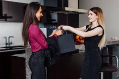 Жизнерадостные элегантные девушки стоя в стильном интерьере с сумками роскошных магазинов счастливыми с их приобретениями Стоковое Фото