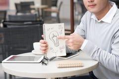 Жизнерадостный азиатский бизнесмен показывая творческие документы идеи стоковое изображение rf