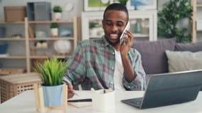 Жизнерадостный Афро-американский фрилансер говорит на мобильном телефоне и использует деятельность ноутбука дома делая далекую ра сток-видео