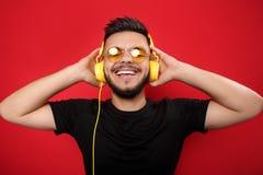 Жизнерадостный бородатый молодой человек нося желтые солнечные очки слушая к музыке с желтыми наушниками на красной предпосылке стоковое изображение rf