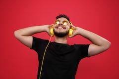 Жизнерадостный бородатый молодой человек нося желтые солнечные очки слушая музыку с желтыми наушниками на красной предпосылке стоковое фото