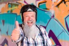 Жизнерадостный бородатый человек при шлем давая большой палец руки вверх стоковые фото