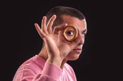 Жизнерадостный взгляд подростка через отверстие бейгл стоковое изображение