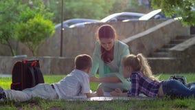 Жизнерадостный воспитатель женщины прочитал книгу для мальчика и девушки сидя на зеленой траве в природе в солнечном свете позже сток-видео