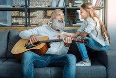 Жизнерадостный дед поя для его прелестной внучки стоковое фото