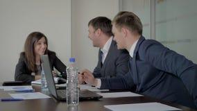Жизнерадостный директор и менеджеры на столе переговоров смеясь обсуждающ идеи сток-видео