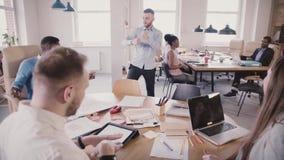 Жизнерадостный европейский молодой главный исполнительный директор празднуя успех с танцем потехи в современном офисе, делая колл видеоматериал