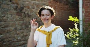 Жизнерадостный жест рукой ОК показа подростка и усмехаясь положение в улице сток-видео