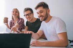 Жизнерадостный и положительный молодой смеяться сотрудников Они сидят на таблице в белой комнате Люди смотрят экран ноутбука Моло стоковое фото rf