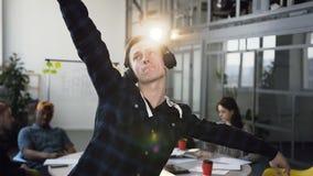 Жизнерадостный и счастливый бизнесмен активно танцует пока слушая музыка на офисе рядом с коллеги Он носит сток-видео