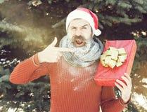 Жизнерадостный красивый человек в шляпе Санта Клауса, бородатом хипстере с бородой и усике предусматриванном с белым заморозком,  стоковое фото