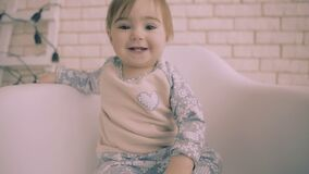 Жизнерадостный маленький ребёнок брюнет сидя на белом стуле с замедленным движением улыбки видеоматериал
