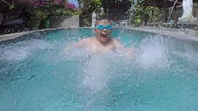 Жизнерадостный мальчик брызгая воду в бассейне