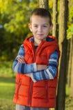 Жизнерадостный мальчик в красном жилете в древесинах Стоковые Фото
