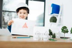 Жизнерадостный мальчик в трудной шляпе показывая изображение дома Стоковая Фотография RF
