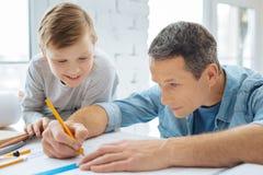 Жизнерадостный мальчик наблюдая его светокопию эскиза отца в офисе Стоковые Изображения RF