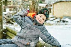 Жизнерадостный мальчик на прогулке зимы, одетой в куртке и шляпе стоковое изображение rf
