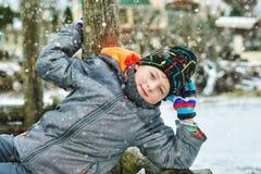Жизнерадостный мальчик на прогулке зимы, одетой в куртке и шляпе стоковая фотография rf