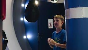 Жизнерадостный мальчик скачет перед грушей игры и поражает сильное дуновение к нему акции видеоматериалы