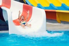 Жизнерадостный мальчик сползая в воду в парке aqua стоковое изображение