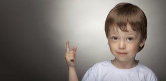 Жизнерадостный мальчик указывая вверх, счастливый ребенок с хорошей идеей стоковые изображения rf