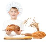 Жизнерадостный мальчик хлебопека с хлебцем хлеба рожи стоковое изображение