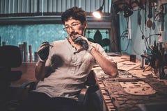 Жизнерадостный мастер на его мастерской restouration с курсирует и мир стекла в его руках стоковое изображение rf