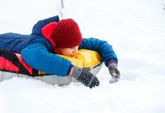 Жизнерадостный милый молодой мальчик в шарфе и синем пиджаке оранжевой шляпы красных держит трубку на снеге, имеет потеху, улыбки стоковое фото
