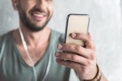 Жизнерадостный милый парень использует его мобильный телефон Стоковые Фотографии RF