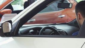 Жизнерадостный молодой красивый человек усмехаясь к камере сидя в его новом автомобиле видеоматериал