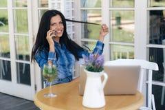 Жизнерадостный молодой студент сидит в кафе, говоря на телефоне с подругой, выпивая вкусные пить, усмехаясь стоковые изображения