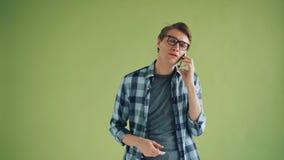 Жизнерадостный молодой человек говоря на мобильном телефоне и показывая жестами на зеленой предпосылке видеоматериал