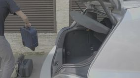 Жизнерадостный молодой человек принимая багаж от хобота припаркованного автомобиля приезжая на концепцию автомобильного путешеств видеоматериал