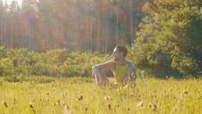 Жизнерадостный молодой человек сидит на зеленой траве в лете и улыбках акции видеоматериалы